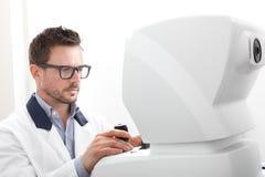 Optician with keratometer, optometrist doctor examines eyesight, isolated on white. Optician with keratometer, optometrist doctor examines eyesight, on white royalty free stock photos