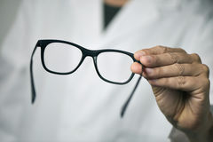 Optician man bringing a pair of eyeglasses. Closeup of a young optician man bringing a pair of eyeglasses to the observer Stock Photos