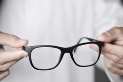 Optician man bringing a pair of eyeglasses. Closeup of a young optician man bringing a pair of eyeglasses to the observer Royalty Free Stock Photos