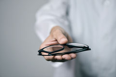 Optician man bringing a pair of eyeglasses. Closeup of a young optician man in a white coat bringing a pair of eyeglasses to the observer Royalty Free Stock Image
