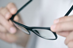 Optician man checking a pair of eyeglasses. Closeup of a young optician man in a white coat checking a pair of eyeglasses Stock Image