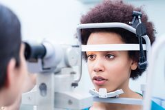 Optician measuring women eyes with refractometer Royalty Free Stock Images