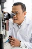 Optician with microscope Royalty Free Stock Photos