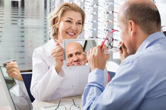 Optician offering glasses frames to client Royalty Free Stock Image