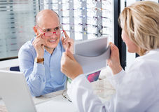 Optician offering glasses frames to client Stock Image