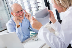 Optician offering glasses frames to client Royalty Free Stock Images