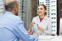 Optician offering glasses frames to customer Royalty Free Stock Images