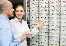 Optician offering glasses frames to customer Stock Photography