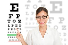 Optician / Optometrist. Optician or optometrist pointing at Snellen eye exam chart. Woman eye doctor wearing glasses on white background. Female Caucasian / stock image
