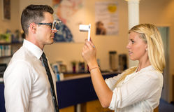 Optician or optometrist measuring the eye distance of a customer Stock Photo