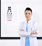 Optician / Optometrist. Optician or optometrist pointing at Snellen eye exam chart. Woman eye doctor wearing glasses on white background. Female Caucasian / stock photos