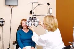 Optician preparing senior for eye exam Stock Photos