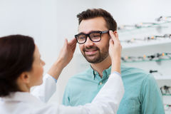 Optician putting on glasses to man at optics store royalty free stock images