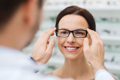 Optician putting glasses to woman at optics store Stock Photo