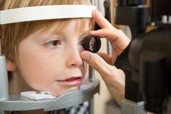 Optician's Hand Examining Boy's Retina. Closeup of male optician's hand examining boy's retina with lens in clinic Royalty Free Stock Image