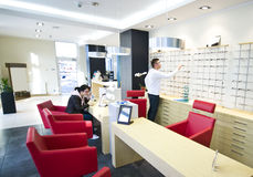Optician shop. Salesman serving female client at optician shop royalty free stock photo