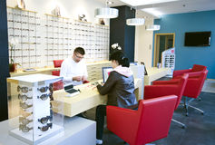 Optician shop. Salesman serving female client at optician shop royalty free stock photography