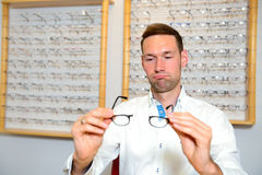 In optician shop- young man with broken glasses Stock Photo