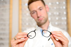 In optician shop- young man with broken glasses Royalty Free Stock Photography
