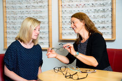 In optician shop- young woman selecting new glasses Royalty Free Stock Image