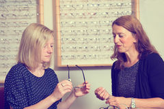 In optician shop- young woman selecting new glasses Royalty Free Stock Photos
