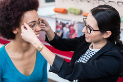 Optician showing woman new glasses Royalty Free Stock Images