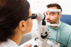 Optician with slit lamp and patient at eye clinic. Health care, medicine, people, eyesight and technology concept - close up of optometrist with slit lamp Royalty Free Stock Images