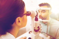 Optician with slit lamp and patient at eye clinic Stock Photo