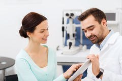Optician with tablet pc and patient at eye clinic Royalty Free Stock Photography