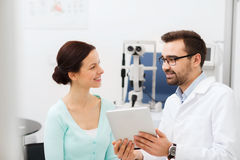 Optician with tablet pc and patient at eye clinic Stock Photo