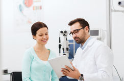 Optician with tablet pc and patient at eye clinic Royalty Free Stock Photos