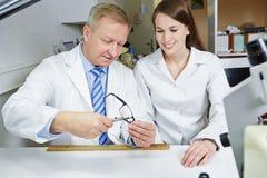 Optician teaching apprentice stock images