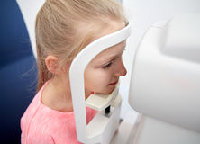 Optician with tonometer and patient at eye clinic. Health care, medicine, people, eyesight and technology concept - optometrist with non contact tonometer royalty free stock images