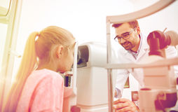 Optician with tonometer and patient at eye clinic. Health care, medicine, people, eyesight and technology concept - optometrist with non contact tonometer stock photo