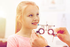 Optician with trial frame and girl at clinic. Health care, medicine, people, eyesight and technology concept - optometrist with trial frame checking girl patient Royalty Free Stock Photography