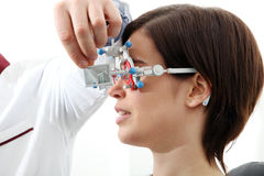 Optician with trial frame, optometrist doctor examines eyesight. Of woman patient stock image