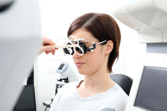 Optician with trial frame, optometrist doctor examines eyesight. Of woman patient Royalty Free Stock Photo