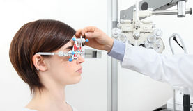 Optician with trial frame, optometrist doctor examines eyesight Royalty Free Stock Images