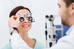 Optician with trial frame and patient at clinic. Health care, medicine, people, eyesight and technology concept - optometrist with trial frame checking patient Stock Photos