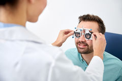 Optician with trial frame and patient at clinic. Health care, medicine, people, eyesight and technology concept - optometrist with trial frame checking patient royalty free stock photo
