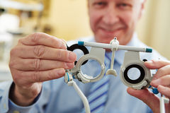 Optician with trial frame. To determine prescription values of glasses stock photography
