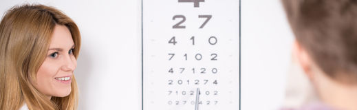 Optician using Snellen test Royalty Free Stock Image