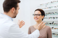 Optician and woman in glasses at optics store Royalty Free Stock Images