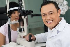 Optician at work. Portrait of successful oculist looking at camaer awith his patient on background Stock Image