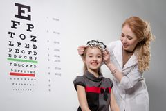 Optician. Young girl smiling while undergoing eye test with phoropter Royalty Free Stock Photos