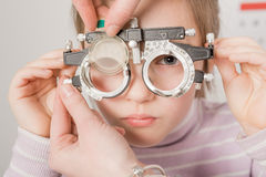 Optician. Young girl smiling while undergoing eye test with phoropter Stock Image