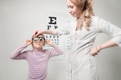 Optician. Young girl undergoing eye test with phoropter Royalty Free Stock Photo