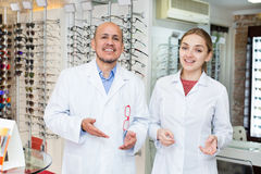 Opticians near stand with spectacles Royalty Free Stock Images