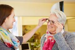 Opticien conseillant la femme supérieure Image stock