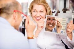 Opticien de femme consultant le client masculin mûr au sujet des cadres Image stock